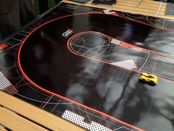 AnkiDrive ist eine Rennbahn, auf der KI-gesteuerte Flitzer herumrasen, die der menschliche Spieler in einer Kampfsimulation mit seinem Fahrzeug von der Strecke fegen kann (Bild: J.G.Weber)