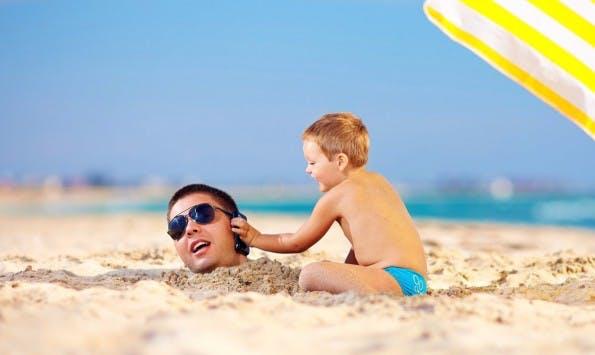 """Auch Smartphones sollten gut vor Hitze und der Sonne geschützt werden – aber auch vor Sand und Wasser. (Foto: <a href=""""http://www.shutterstock.com/de/pic-157057139/stock-photo-happy-kid-helping-father-in-sand-talk-on-the-mobile-phone.html"""">Shutterstock</a>)"""