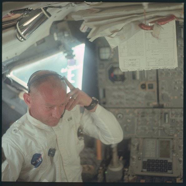 Buzz Aldrin im Inneren der Apollo-11-Raumfähre. Im Hintergrund ist rechts unten das DSKY-Bedienpanel des Apollo Guidance Computers zu erkennen. (Quelle: NASA)