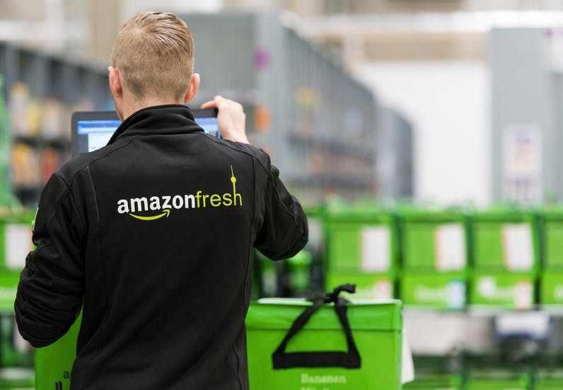 Ein Mitarbeiter des Lebensmittellieferdienstes Amazon Fresh steht im Depot der Firma in Berlin. (Foto: dpa)