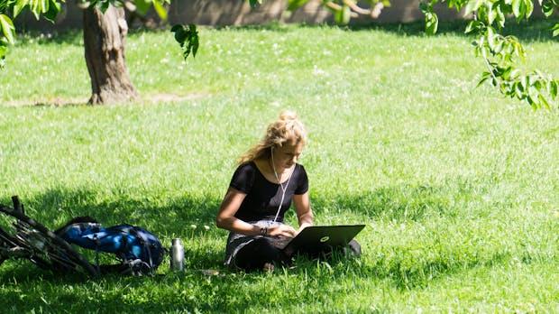 Coliving: Menschen mit Laptop am Dorfteich