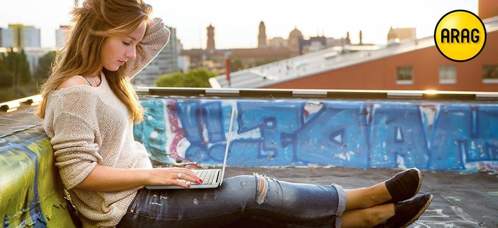 FRrau mit Laptop auf einem Hausdach