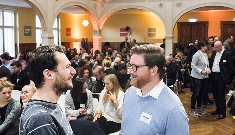 Zwei Herren unterhalten sich im gefüllten Saal. Im Hintergrund zwei sich austauschende Damen und weitere Gespräche