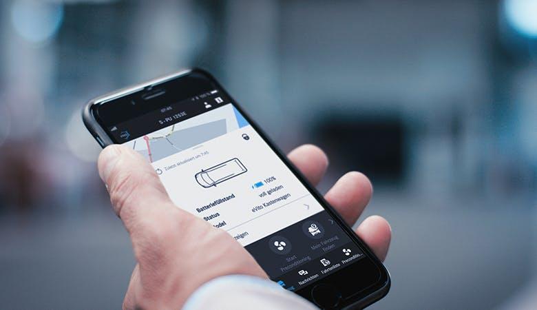 Ein Apple-Smartphone in der Hand eines Nutzers zeigt die für den eVito verfügbare App für Android oder iOS