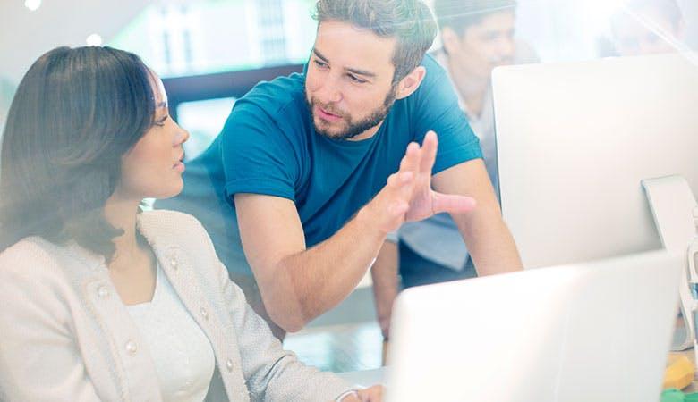 Zwei moderne Büroarbeiter diskutieren vor einem aufgeklappten Laptop