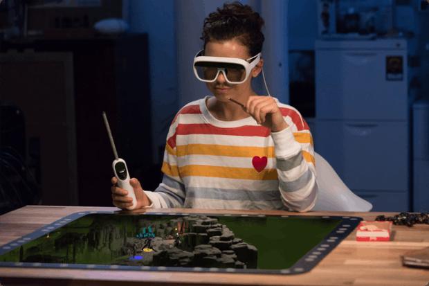 Spieler mit Wand-Controller und AR-Brille vor Tilt-Five-Spielbrett.
