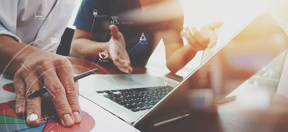 Zwei junge Menschen am Laptop, diskutieren und arbeiten im Internet