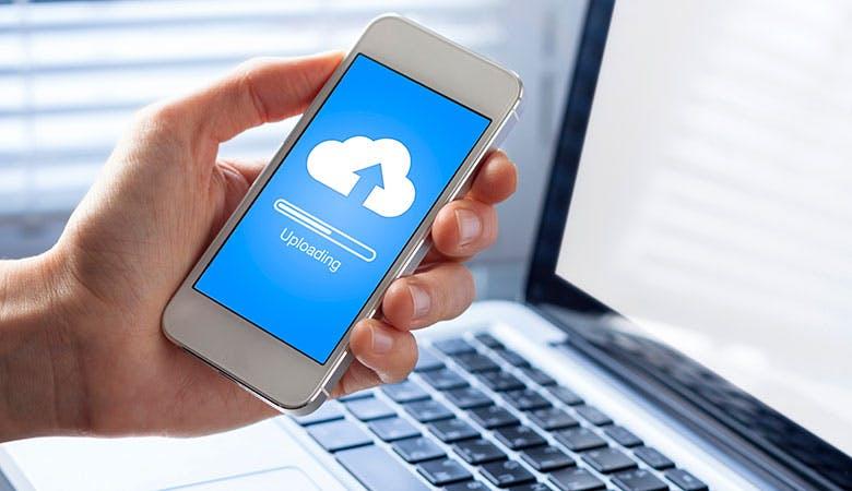 Ein Smartphone wird vor einem Laptop in der Hand gehalten; auf dem Bildschirm ist ein Upload zu sehen