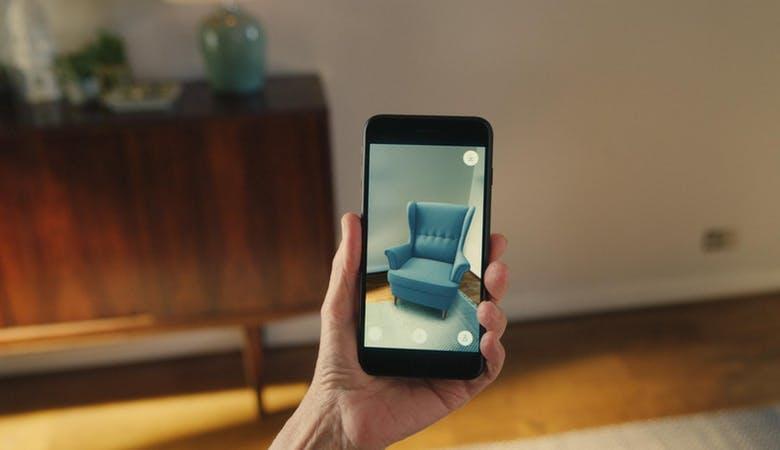 Eine App zeigt durch AR-Technologie einen Sessel, wie er im von der Handykamera gefilmten Bereich des Zimmers aussehen würde