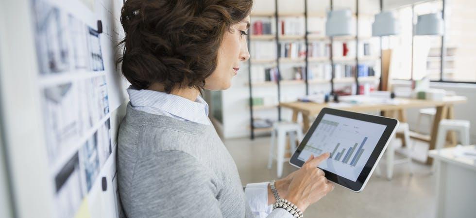 Adrette Business-Frau steht in Tageslicht-Büro und bedient ein Tablet