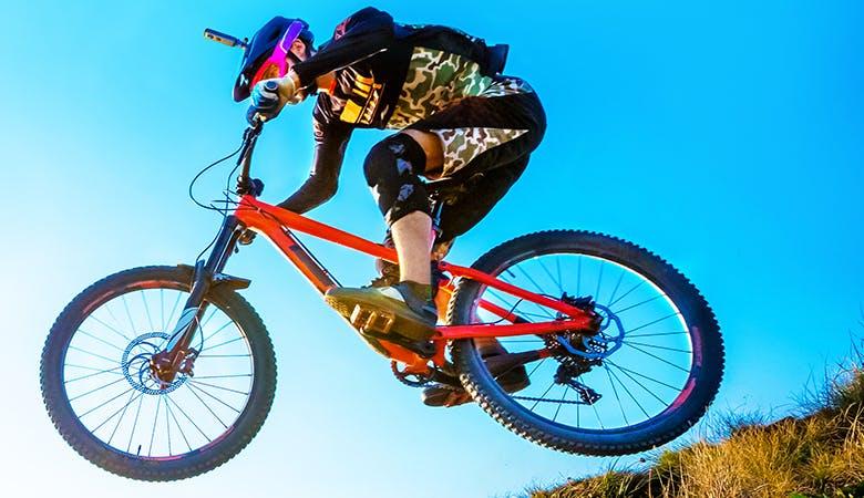 Ein Mountainbiker mit Helmkamera vor blauem Himmel, leichter Sprung