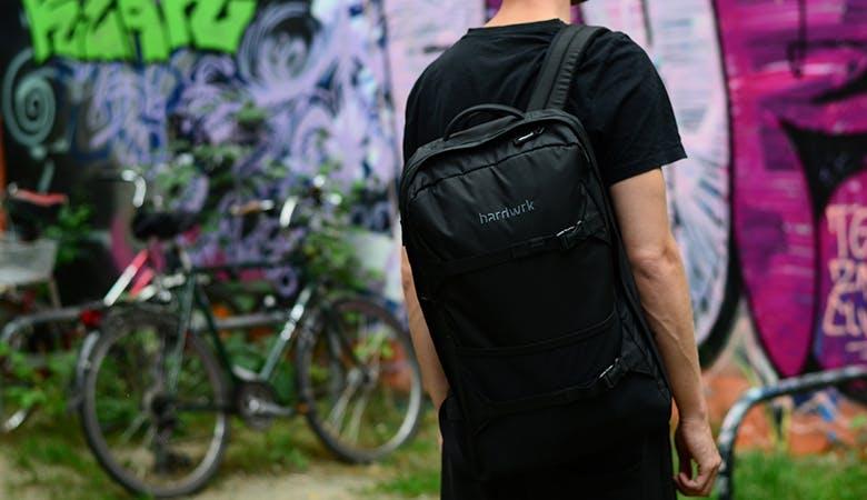 Ein junger Mann steht mit dem Rücken zum Betrachter, der Rucksack im Fokus. Im Hintergrund Fahrräder vor einer mit Graffiti besprühten Wand