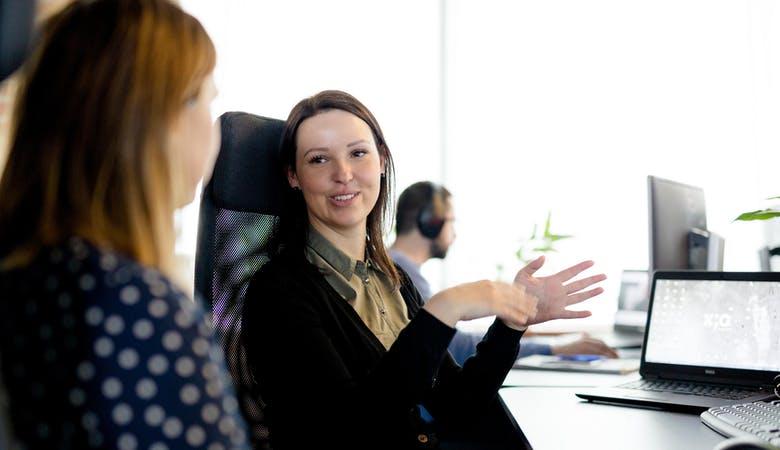Zwei junge Frauen sitzen am Schreibtisch, Laptop im Hintergrund, unterhalten sich