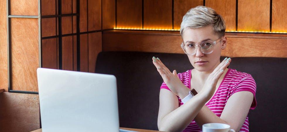 Eine junge Frau mit kurzen, blonden Haaren kreuzt verneinend die Arme vor der Brust, sitzt vor einem Laptop