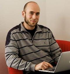 Anton Weste mit Laptop auf einem Sessel.