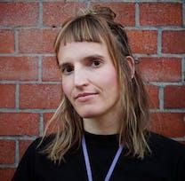 Kathrin Stoll vor Backstein-Mauer.