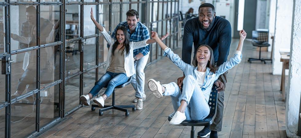 Junge Arbeitskollegen veranstalten ein Bürostuhl-Rennen im modernen Office