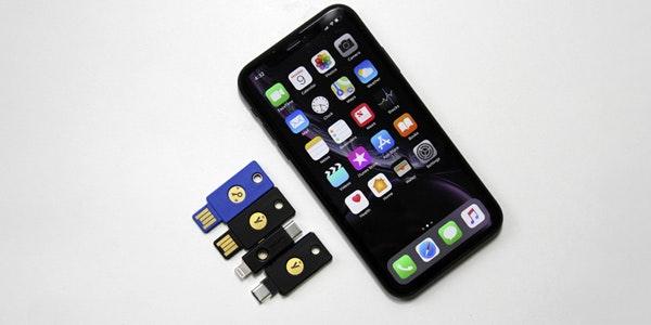 Vier Yubikey-Schlüssel neben iPhone.