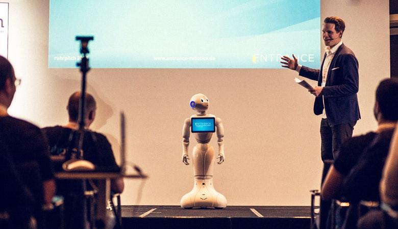 Sebastian Holtze auf der Bühne vor einer Leinwand, neben ihm ein kleiner Roboter mit Bildschirm auf der Brust