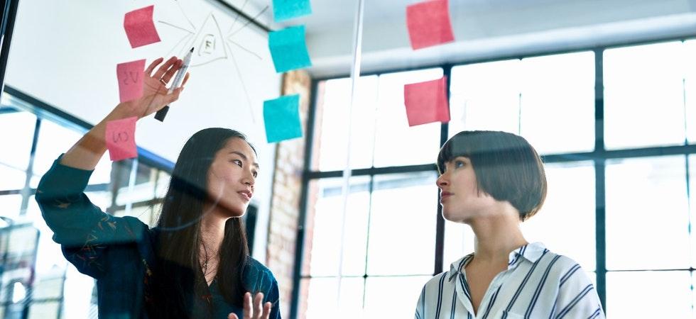 Zwei junge Frauen im Büro, vor Glaswand mit Post-its und mit schwarzem, wasserlöslichen Marker in der Hand