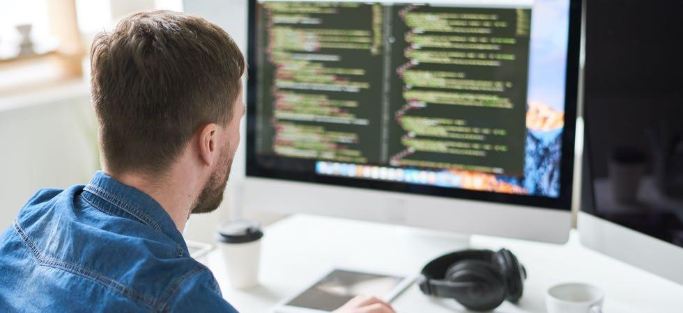 Ein junger Developer mit Kurzhaaarfrisur sitzt im blauen Jeanshemd an seinem Schreibtisch. Darauf ein To-Go-Kaffeebecher, eine Tasse und Over-Ear-Kopfhörer.